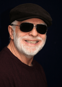 Color head shot wearing brown cap, sunglasses, and wine colored sweater. The author is smiling. He has a white beard.