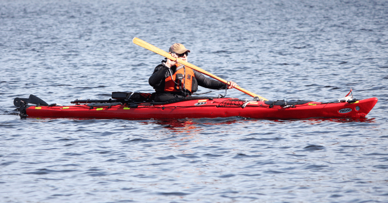 H. N. Henry, wearing neoprene paddling top,spray skirt, life jacket, cap, and sun glasses, is in his red 17 foot Kodiak Prijon sea kayak. The rudder is up and parked at the back. Spare paddles and a solid foam paddle float are on the deck behind him. On the bow of the kayak is white plastic paddle park and next to it is a red wind direction indicator made out a reused pen casing and a ribbon. His paddle is a Greenland style wooden paddle the author made from a 2 X 6 piece of spruce. The author chose this kayak because it carries a heavy load, is almost indestructible, and it is 99.98% recyclable.
