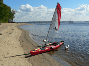 The kayak's nose is resting on the beach of Isle Saint Quentin near mouth of the Saint Maurice River where it empties into the Saint Lawrence. A 24 square foot red and white sail with a lower transparent plastic section is stepped on the kayak forward of the cockpit near the front access hatch. Removable white inflatable outrigger spoons are attached behind the kayak cockpit. An old black plastic slip-on hockey-stick blade is being used as a lee board. The wooden paddle is resting in its park. In the distant background canoeists are paddling to the Saint Lawrence River.